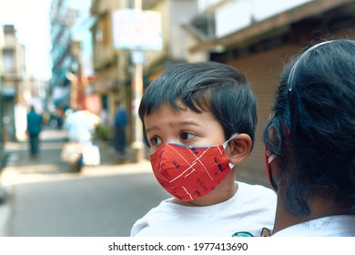 Expressive portrait of a cute baby girl in her mother's arm, walking in street. Both of them are wearing protective face mask due to Covid-19 pandemic.