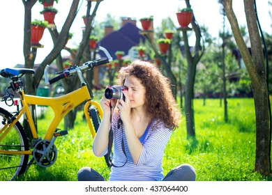 Expressive portrait of happy young girl holding camera. Happy young lady relaxing on a green