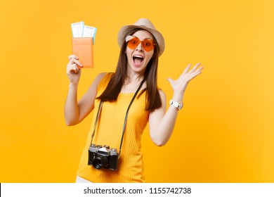 Expressive tourist woman in summer casual clothes, hat holding passport, tickets isolated on yellow background. Female traveling abroad to travel on weekends getaway. Air flight journey concept