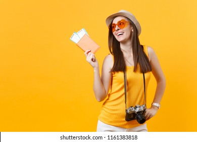 Expressive tourist woman in summer casual clothes, hat holding passport, tickets isolated on yellow orange background. Female traveling abroad to travel weekends getaway. Air flight journey concept