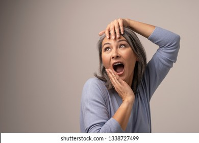 Expressive Woman Poses And Screams Out Loud. Beautiful Middle-Aged Woman Widely Opens Her Mouth And Touches Her Head Posing For The Camera. Portrait. Horizontal Shot