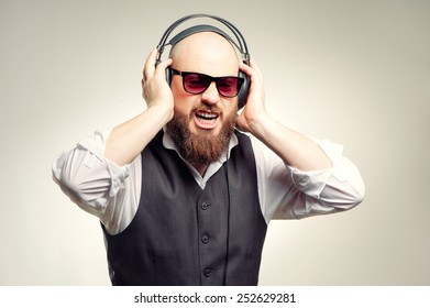 Expressive young bearded man in headphones standing against grey background listening to the music and sing
