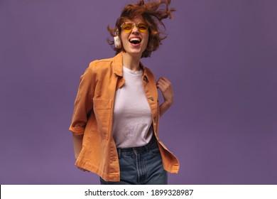 Ausdrucksvolles, junges Brennottentanz auf violettem Hintergrund. Attraktives, dunkelhaariges, lockiges Mädchen in orangefarbenem Hemd, weißes Oberteil und stilvolle Brillen, Kopfhörer tragen, Musik hören und genießen