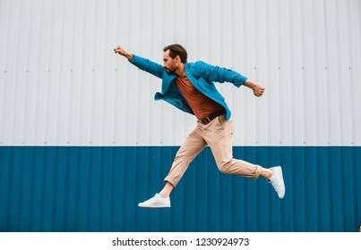 Expressive young man in casual clothes putting one fist up while pretending to be a superman and jumping high