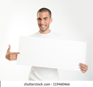 Expressive young man holding a blank board ideal for inserting your own message