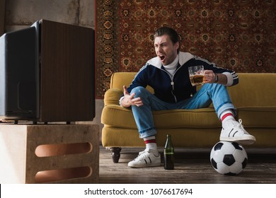 expressive young man in vintage clothes with ball and mug of beer watching soccer on old tv and shouting
