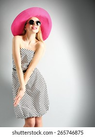 Expressive young model in pink hat with sunglasses on gray background