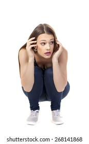 Expressive young woman crouching down in fear over a white background.