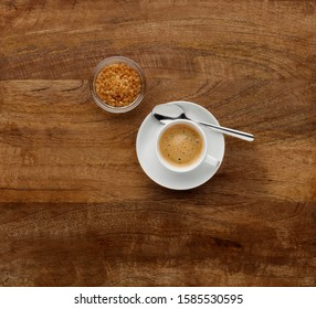 An expresso coffee, shot on a dark wooden background, with brown sugar in a bowl, with space for copy