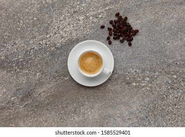 An expresso coffee, shot on a grey stone background, with a handful of coffee beans, with space for copy