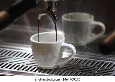 An expresso machine in the midst of pouring into a coffee cup