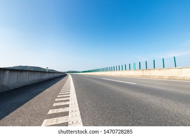 expressway and asphalt road surface against a sunny sky