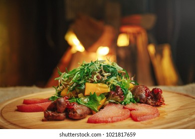 exquisite salad with mango and meat wooden background, table setting, cozy restaurant serve on the background of the fireplace close-up.