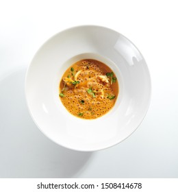 Exquisite serving airy cream bisque with seafood on white restaurant plate isolated. Smooth, creamy, highly seasoned soup based on a crustaceans broth, high cuisine molecular dish with sea food
