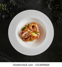 Exquisite Serving Creative Restaurant Food with Grilled Tiger Prawns and Smoked Sweet Pepper Cream Top View. Beautiful Elegant Decorated Italian Pasta with Big King Shrimps on Black Marble Table