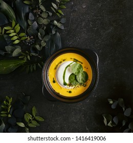 Exquisite Serving Pumpkin Cream Soup with Ricotta Cheese Mousse Top View. Beautiful Creative Molecular Italian Dish with Stylish Decorations of Dark Plants on Natural Black Stone