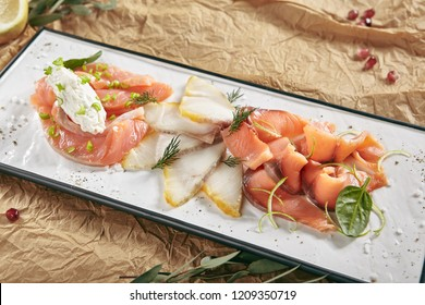 Exquisite Serving Restaurant Plate of Smoked Salted Raw White Fish Fillet with Red Fish Sashimi. Delicacy Fresh Seafood Dish with Toothfish, Salmon and Tuna Meat on Rustic Background Close Up