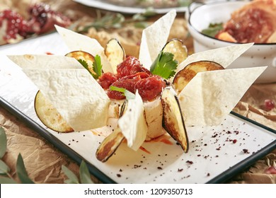 Exquisite Serving White Restaurant Plate of Eggplant Paste decorated With Eggplant Chips and Thin Slices of Pita Bread. Baba Ghanoush, Caponata, or Aubergine Caviar with Mashed Grilled Aubergines