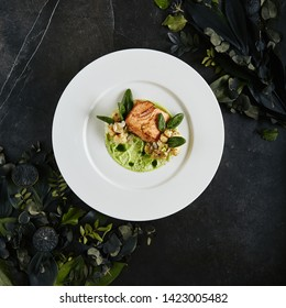 Exquisite Serving White Restaurant Plate with Fillet of Salmon 48 Degrees, Green Peas Cream and Burnt Cauliflower Top View. Stylish Italian Seafood Dish on Natural Black Marble Background
