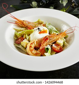 Exquisite Serving White Restaurant Plate of Caesar Salad with Shrimps, Chicken, Croutons, Tomatoes, Cucumbers Top View. Beautiful Delicacy Seafood Cesar Salat on Black Marble Background