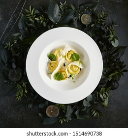Exquisite Serving White Restaurant Plate of Homemade Crab Dumplings with Sour Cream Sauce and Black Truffle Top View. Seafood Ravioli on Natural Dark Leaves, Flowers and Fruits Background