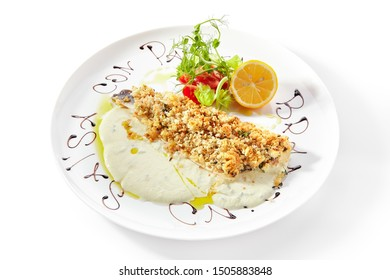 Exquisite serving white restaurent plate of breaded pike perch or zander fillet with cream sauce isolated closeup. Restaurant main course with fried sander fish or pike meat with lemon and greens