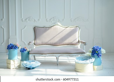 Exquisite sofa in a beautiful interior.Classical interior with sofa.Exquisite sofa in a white interior with adornments of beautiful blue flowers