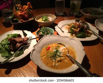 Exquisite Thai meal featuring crab curry, green mango salad, assorted relishes, fried mushrooms, and grilled beef salad.