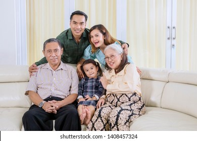 Extended Asian family looks happy while hugging together and taking a group selfie picture at home