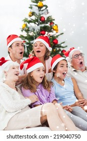 Extended family singing christmas carols against snow falling