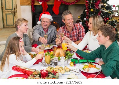Extended family toasting at christmas dinner at home in the living room