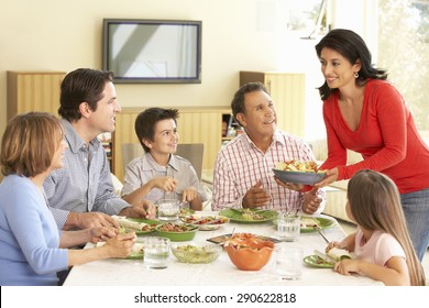 Extended Hispanic Family Enjoying Meal At Home