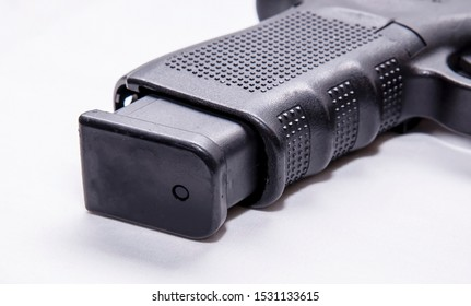 An extended pistol magazine out of the grip of a black semi automatic 9mm pistol on a white background