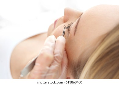 Extending eyelashes in the beauty salon.The beautician prolongs and thickens eyelashes.