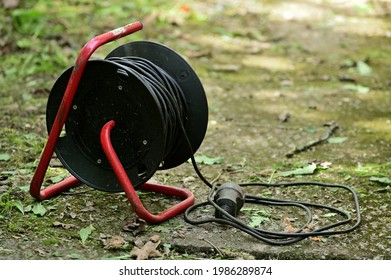 Extension cord on reel with bracket. Part of the wire is wound and lies nearby. The bracket rests on concrete slabs.