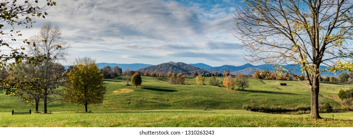 Extensive pastures of horse farm in Albemarle County, in central Virginia, with Blue Ridge Mountains in far distance and Fox Mountain center.