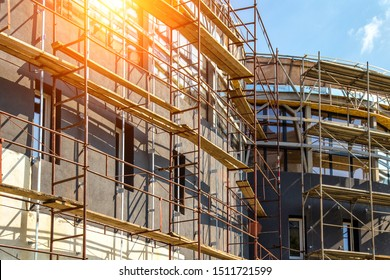 Extensive scaffolding providing platforms for work in progress on a new apartment block,Tall building under construction with scaffolds,Construction Site of New Building