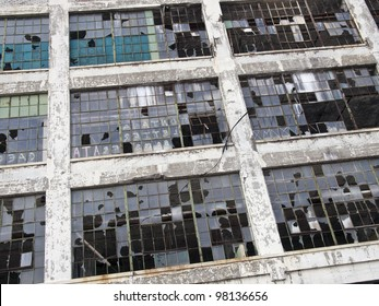 Exterior of an abandoned automobile manufacturing plant in Detroit Michigan. Most of the windows are broken.