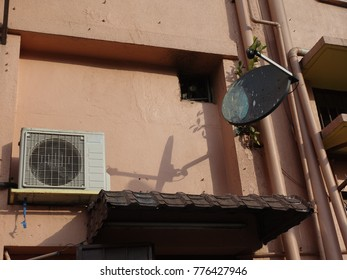 exterior air conditioning compressor on building wall with selective focus on street photography subject.