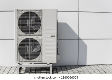 Exterior air conditioning unit on a wall.