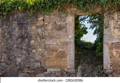 Exterior of ancient ruined stone building. Old abandoned house with empty entrance and grass. Ruined brick house with door. Ivy on stone wall of antique house. Medieval architecture. History concept.