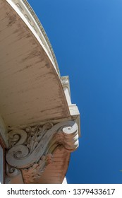 Exterior architecture curved balcony with carved corbel, blue sky copy space, vertical aspect