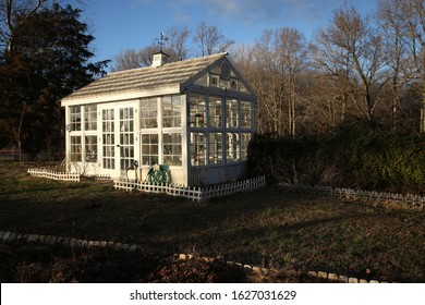 Exterior of a beautiful custom built white Victorian style greenhouse with cupola and weathervane