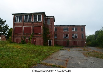 Exterior of boarded up and abandoned brick asylum hospital building