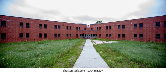 Exterior of brick cellblock with overgrown yard in abandoned prison.