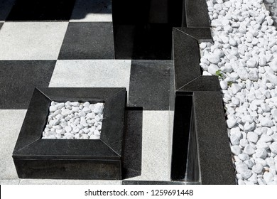 the exterior is a building with square paving slabs and marble beds on the ground and on a black marble wall decorated with white round pebbles.