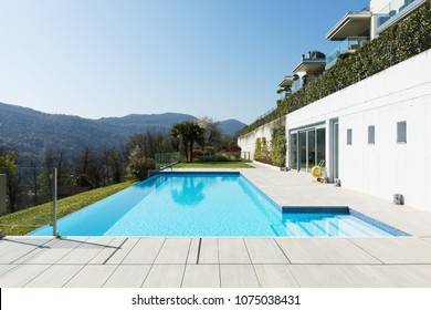 Exterior of building with swimming pool overlooking the hills. Sunny day