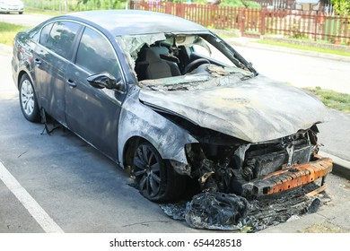 The exterior of a burned out car at a parking lot.