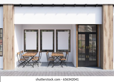 Exterior of a cafe with white walls, three posters hanging on them and wooden tables with chairs. 3d rendering, mock up