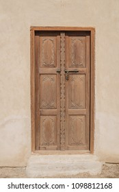 An exterior carved wooden door and step of a restored traditional arabian house.